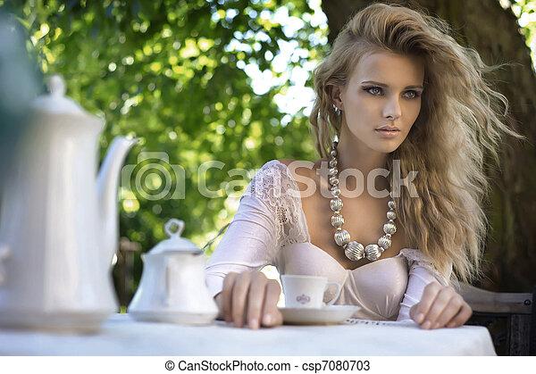 Junge Schönheit am Mittagstisch im Garten - csp7080703