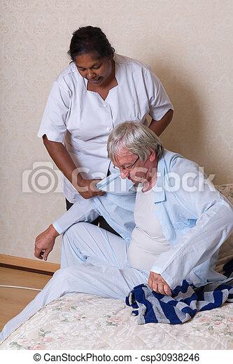 Schwester hilft älteren Menschen beim Anziehen. - csp30938246