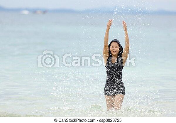 Thai-frau spielt auf see. Eine junge thai-frau, die in
